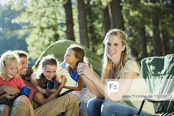 Smiling family relaxing at campsite in woods