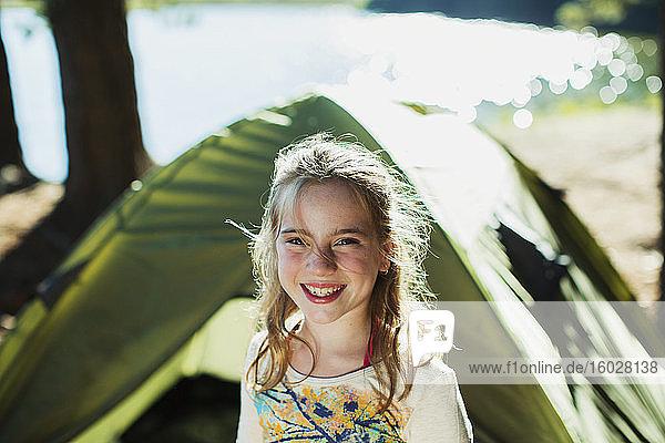 Lächelndes Mädchen vor dem Zelt