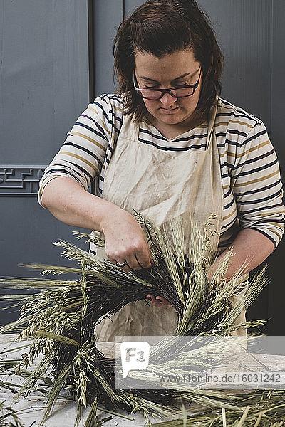 Frau macht einen Winterkranz  fügt getrocknete Gräser und Samenköpfe und Zweige mit braunen Blättern hinzu.