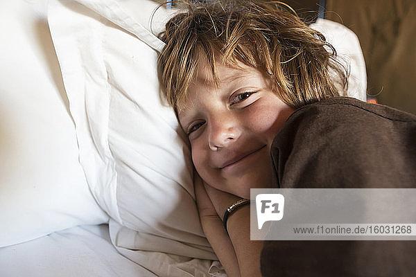 Ein lächelnder 5 Jahre alter Junge im Bett in seinem Zelt  Kalahari-Wüste.
