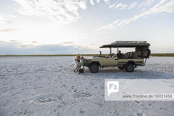 Ein Safarifahrzeug  das in der Abenddämmerung in der Salinenlandschaft geparkt ist.