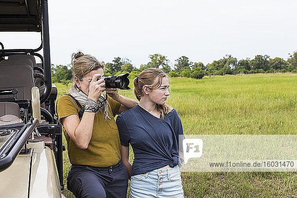 Mutter fotografiert mit Teenager-Tochter in der Nähe eines Safari-Fahrzeugs  Botswana