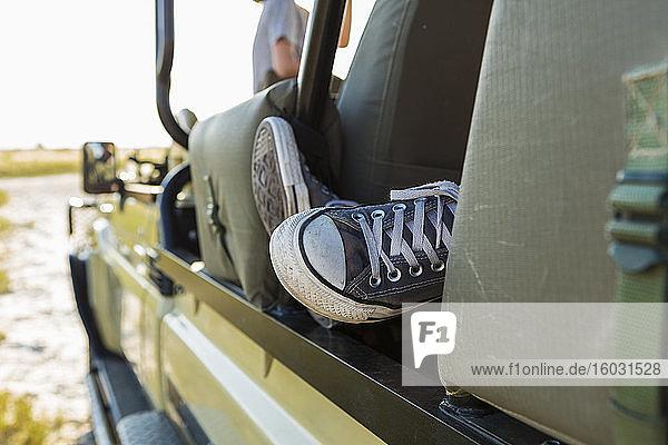 Der Turnschuh einer Person in einem Jeepfenster.