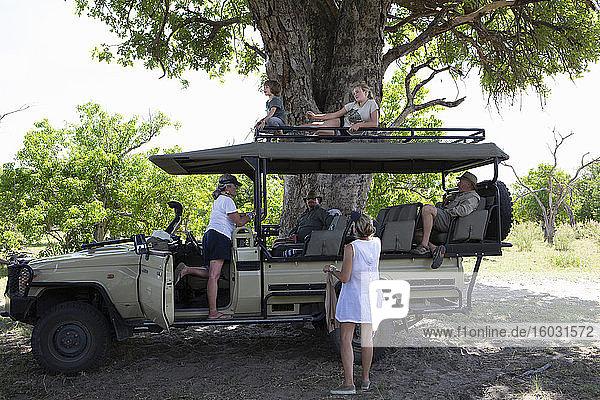Ein im Schatten geparkter Safarijeep mit sechs Familienmitgliedern  die sich ausruhen.