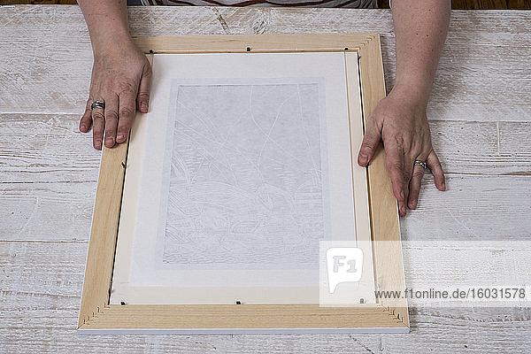 Person  die einen Bilderrahmen um eine Druckgrafik legt.