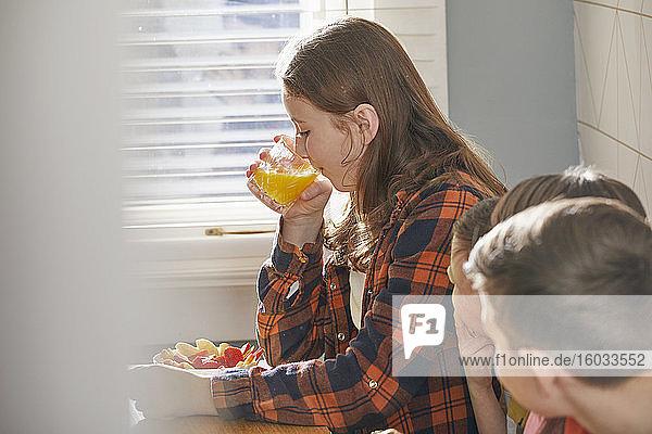 Teenage girl sitting on sofa  eating breakfast  drinking orange juice.