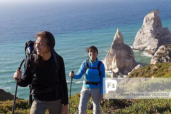 Zwei Frauen mit Rucksäcken und Wanderstöcken  die entlang der Küste mit Blick auf die Schornsteine des Meeres laufen.