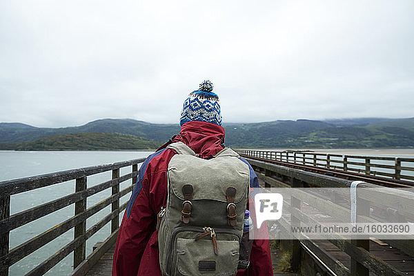 Rückansicht eines Wanderers beim Überqueren der Barmouth Bridge  einem hölzernen Eisenbahnviadukt über die Mündung des Mawddachs  Barmouth