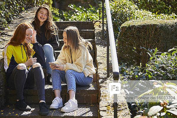 Drei Mädchen im Teenageralter sitzen draußen auf einer Treppe und überprüfen ihr Handy.