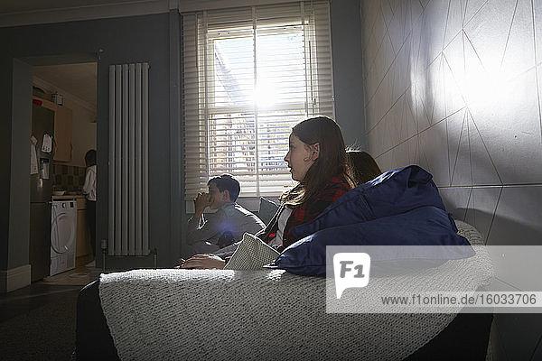 Gruppe von Kindern  die im Pyjama auf einem Sofa sitzen und fernsehen.