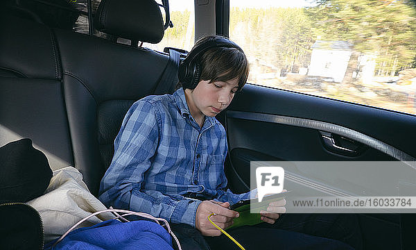 Junge sitzt in einem Auto  trägt Kopfhörer und hält ein digitales Tablet  Vasterbottens Lan  Schweden.
