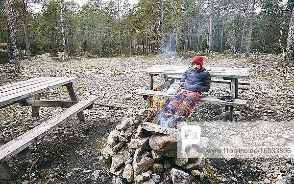 Junge sitzt auf einer Picknickbank neben einem Lagerfeuer in einem Wald in Vasterbottens Lan  Schweden.