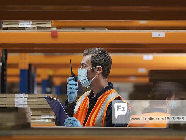 Mann mit chirurgischer Gesichtsmaske und Warnweste bei der Arbeit in einem großen Lagerhaus.