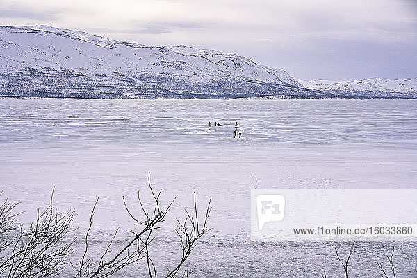 Blick über den zugefrorenen See mit Menschen in der Ferne  Vasterbottens Lan  Schweden.