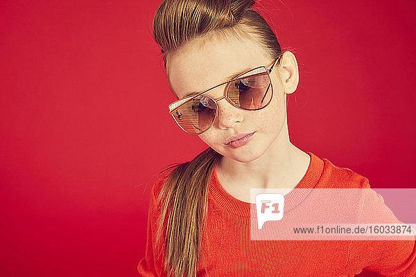 Porträt eines brünetten Mädchens mit rotem T-Shirt und Sonnenbrille auf rotem Hintergrund  das in die Kamera schaut.