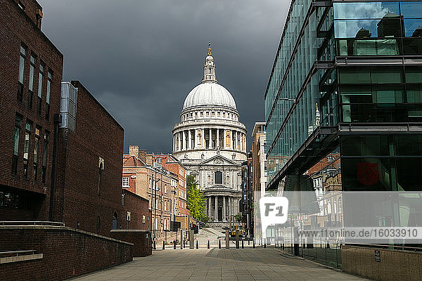 View along empty streets  Peter's Hill and St Paul's Cathedral in London under a storm sky during the Corona virus crisis.