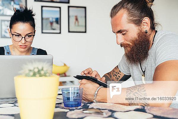 Bärtiger tätowierter Mann mit langen brünetten Haaren und Frau mit langen braunen Haaren sitzen an einem Küchentisch und benutzen Laptop und Mobiltelefon.