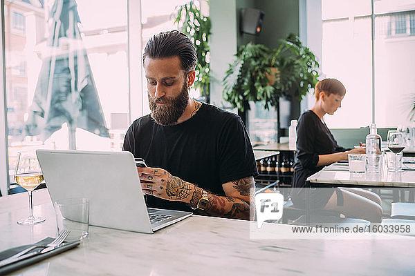Junger bärtiger Mann in schwarzem T-Shirt  der am Tisch in einer Bar sitzt und ein Mobiltelefon und einen Laptop benutzt.