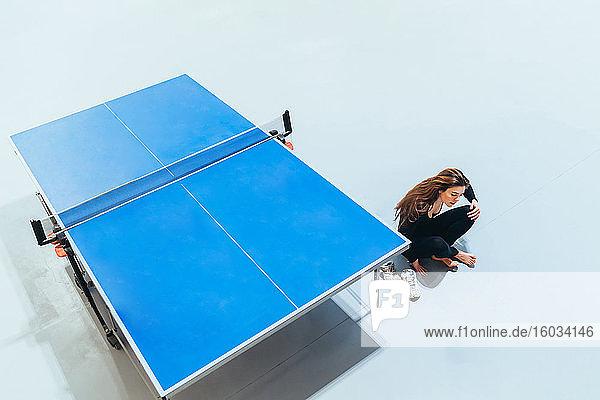 Hochwinkelaufnahme einer Frau  die auf dem Boden neben dem blauen Tischtennistisch sitzt.
