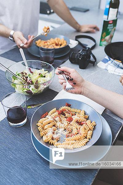 Nahaufnahme aus hohem Winkel von zwei Personen  die an einem Tisch stehen und Schalen mit Fusili-Nudeln essen.