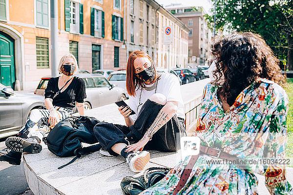 Drei junge Frauen  die während des Corona-Virus Gesichtsmasken trugen  saßen an einem Flussufer und unterhielten sich.