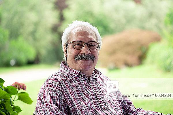 Porträt eines älteren Mannes mit Schnurrbart und Brille  der im Garten sitzt und in die Kamera lächelt.
