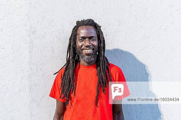 Porträt eines schwarzen Mannes mit Dreadlocks in rotem T-Shirt  der vor einer weißen Wand steht und in die Kamera lächelt.