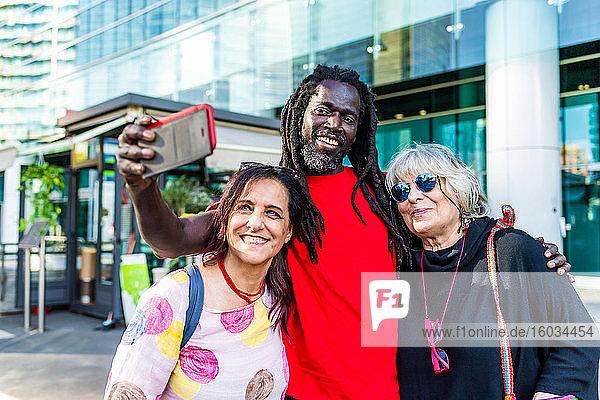 Schwarzer Mann mit Dreadlocks und zwei kaukasische Frauen  die mit dem Handy Selbstgespräche führen.