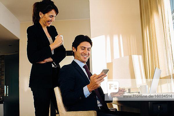 Geschäftsmann und Geschäftsfrau tauschen Textnachrichten im Hotelzimmer aus