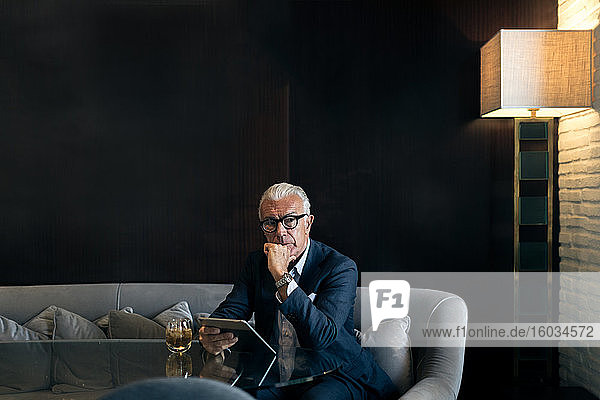 Leitender Geschäftsmann am Hoteltisch sitzend mit digitalem Tablett  Portrait