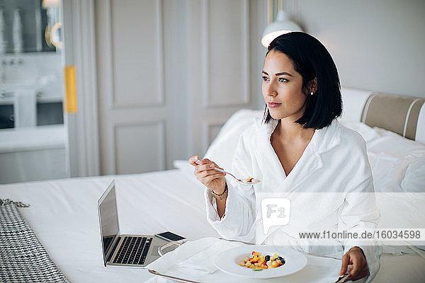 Frau benutzt Laptop und frühstückt in der Suite