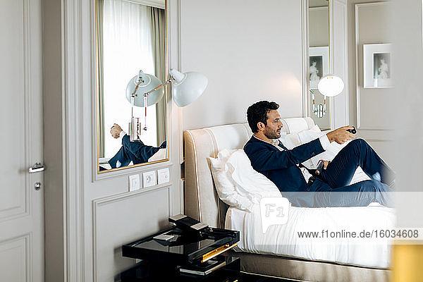 Geschäftsmann mit Fernsteuerung in der Suite