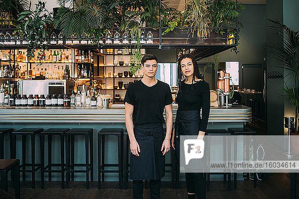 Porträt einer jungen Frau und eines schwarz gekleideten Mannes  die vor der Theke stehen und in die Kamera lächeln.