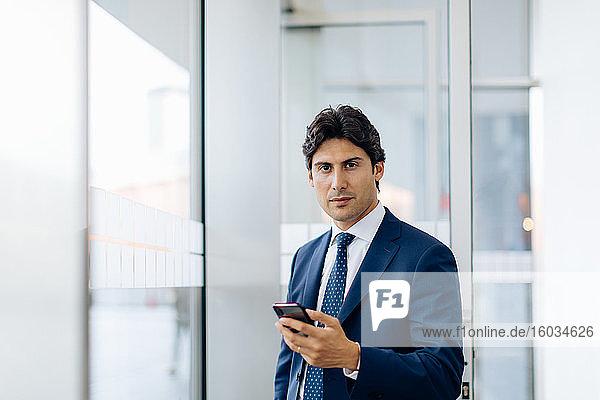 Geschäftsmann benutzt Smartphone im Bürogebäude