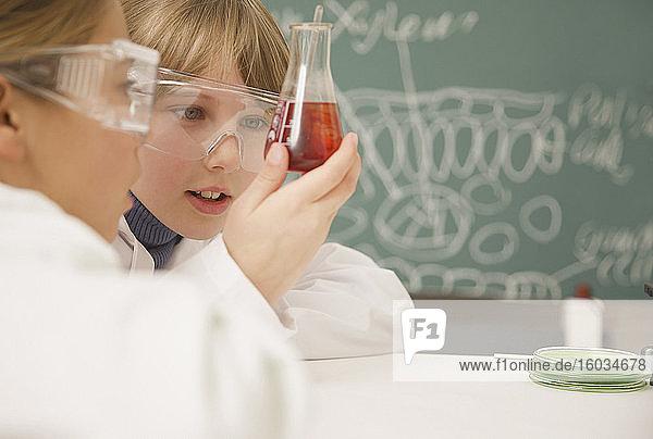 Schüler der Junior-Highschool untersuchen Becher mit Flüssigkeit im naturwissenschaftlichen Unterricht