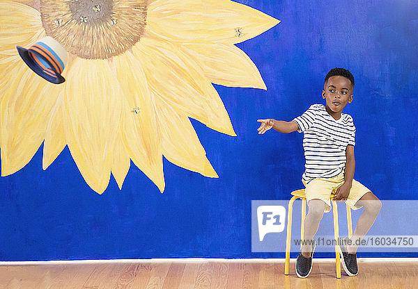 Cooler Junge wirft Mütze vor lebhaftem Sonnenblumenhintergrund