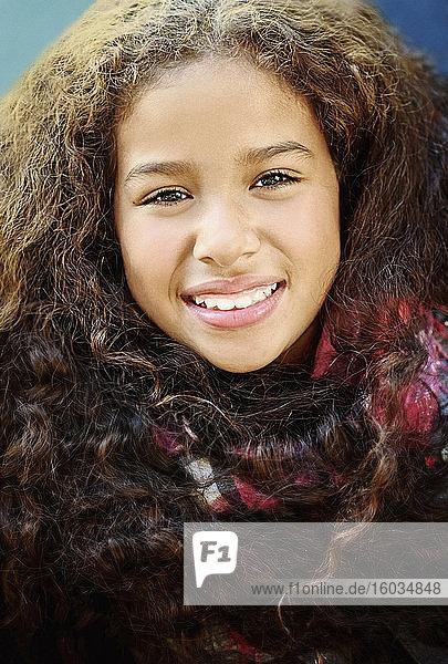 Nahaufnahme eines lächelnden Mädchens mit lockigem schwarzem Haar