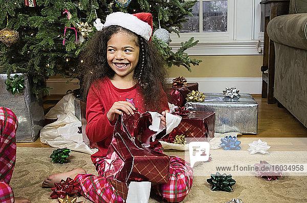 Glückliches Mädchen im Pyjama öffnet Weihnachtsgeschenk am Weihnachtsbaum