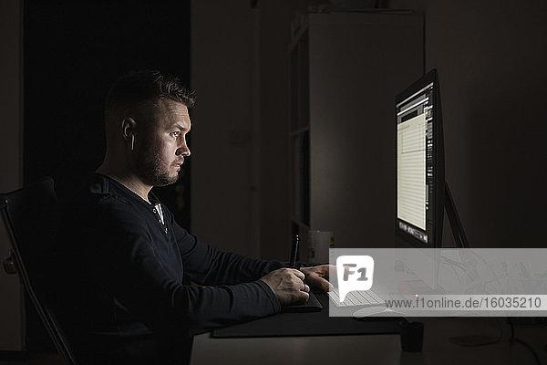 Mann mit Ohrstöpseln arbeitet spät am Computer in einem dunklen Raum