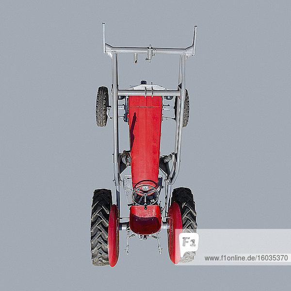 Ansicht von oben: roter Traktor auf blauem Hintergrund