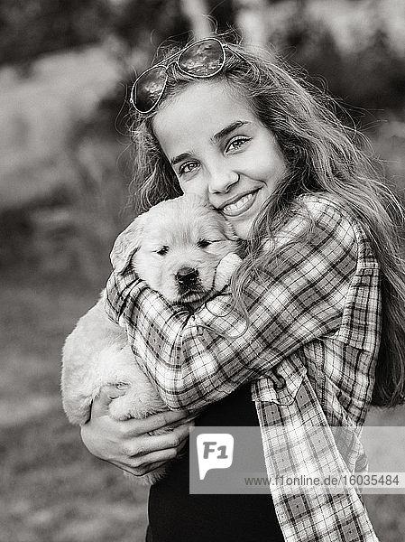 Porträt Teenagerin mit Golden Retriever-Welpe