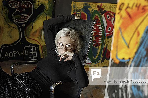 Porträt selbstbewusste junge Künstlerin im Atelier mit Gemälden