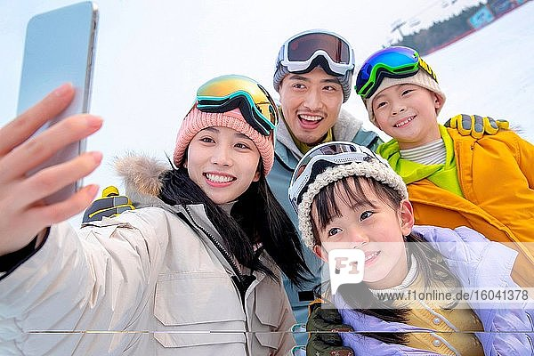 Skifahren auf einer vierköpfigen Familie umarmen zusammen