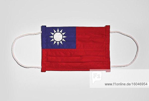Symbolbild Corona-Krise  Mundschutz  Atemschutzmaske  Mund-Nase-Schutz mit Flagge von Taiwan  weißer Hintergrund