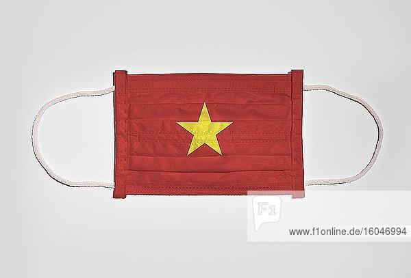 Symbolbild Corona-Krise  Mundschutz  Atemschutzmaske  Mund-Nase-Schutz mit Flagge von Vietnam  weißer Hintergrund