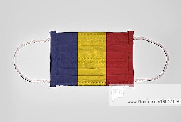 Symbolbild Corona-Krise  Mundschutz  Atemschutzmaske  Mund-Nase-Schutz mit Flagge von Rumänien  weißer Hintergrund