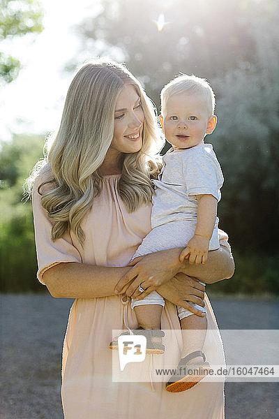 Mutter trägt lächelndes Baby Sohn
