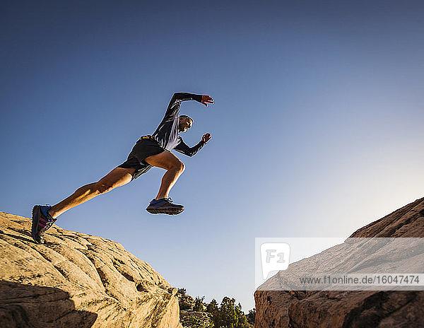 USA  Utah  St. George  Mann springt über Felsen  während er in erodierter Landschaft läuft