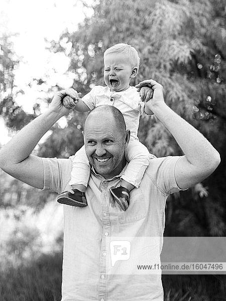 Glücklicher Vater trägt seinen kleinen Sohn auf den Schultern