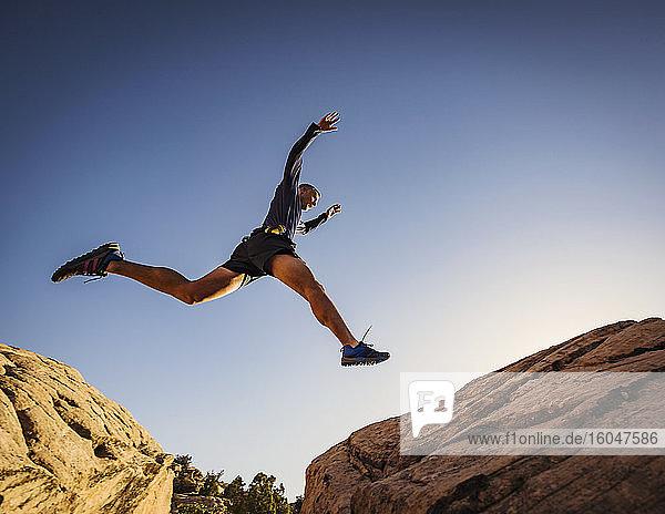 USA  Utah  St. George  Mann springt über Felsen  während er in der Landschaft läuft